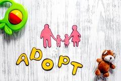 Adoptez le mot, la silhouette de papier de la famille et les jouets sur le copyspace en bois léger de vue supérieure de fond de t Images stock