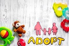 Adoptez le mot, la silhouette de papier de la famille et les jouets sur le copyspace en bois léger de vue supérieure de fond de t Photos stock
