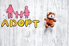 Adoptez le mot, la silhouette de papier de la famille et les jouets sur le copyspace en bois léger de vue supérieure de fond de t Image stock