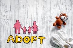 Adoptez le mot, la silhouette de papier de la famille et les jouets sur le copyspace en bois léger de vue supérieure de fond de t Photos libres de droits