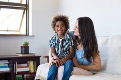 Adoptiertes Kind, das mit Mutter spielt Stockbild