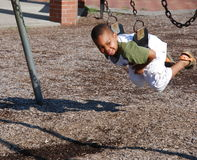 Adoption. A young boy has fun playing on the swings at a local playground Royalty Free Stock Image