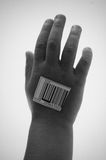 Adoption. Black and white photo of a caucasian child's hand with a barcode label being just another number Royalty Free Stock Photography