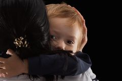 Adoption concept, an orphan is a little boy and his new mother. Happy childhood, caring for children. Sad boy on black background Royalty Free Stock Photography