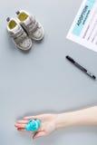 Adoptionform och barnskor på åtlöje för bästa sikt för skrivbordbakgrund upp Arkivbild