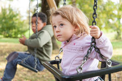 Adoptive brothers on the swing. Adoptive brothers sat on the oscillation stock photography