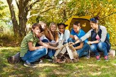 Adoquín feliz de las adolescencias encima de la hoguera junto en sitio para acampar Fotografía de archivo libre de regalías