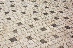 Adoquines de las casillas negras blancas y, un camino viejo pavimentado con la piedra Fondo hermoso Imagen de archivo