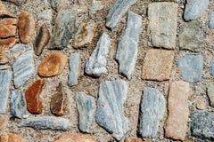 Adoquines de piedra grandes texturizados multicolores hermosos en arena Foto de archivo libre de regalías