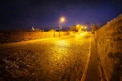 Adoquines entre las paredes de piedra iluminadas por las luces Foto de archivo