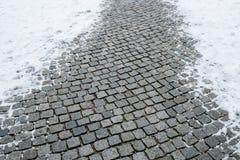 Adoquines mojados con nieve en invierno Fotos de archivo libres de regalías
