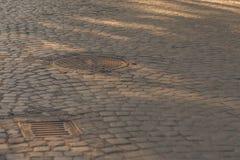 Adoquines viejos del granito con las portillas de la alcantarilla Imagen de archivo libre de regalías