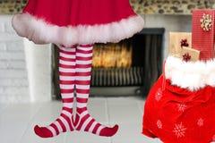 Adorável bonito pouca menina do duende do Natal com os pés pointy que vestem meias listradas do duende e uma posição vermelha do  foto de stock