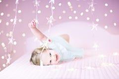 Adoraable-Kleinkindmädchen, das mit ihrem Spielzeugbären zwischen weichen Lichtern in der Sternform spielt Lizenzfreie Stockfotografie
