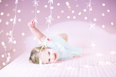 Adoraable toddler girl playing with her toy bear between soft lights in star shape Royalty Free Stock Photography