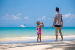 Adorabel daughter and father on sand beach of ocean. Girl drinki Royalty Free Stock Image