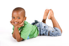Adorable 3 year old black or African American boy. With a big smile lying on the floor with his feet up looking at you Stock Photo