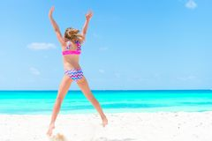 Amazing little girl at beach having a lot of fun on summer vacation. Adorable kid jumping on the seashore. Adorable active little girl at beach during summer Royalty Free Stock Images