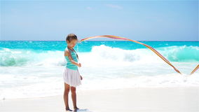 Adorable active little girl playing with gymnastic ribbon on the beach. SLOW MOTION stock video
