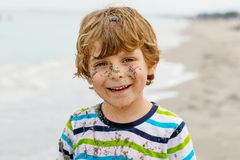 Adorable active little kid boy having fun on beach of North Sea in Germany. Happy cute child relaxing, playing and royalty free stock photos