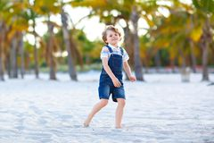 Adorable active little kid boy having fun on Miami beach, Key Biscayne. Happy cute child relaxing, playing with sand and. Enjoying sunny warm day near palms and stock photos
