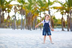 Adorable active little kid boy having fun on Miami beach, Key Biscayne. Happy cute child relaxing, playing with sand and. Enjoying sunny warm day near palms and stock photography