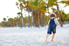 Adorable active little kid boy having fun on Miami beach, Key Biscayne. Happy cute child relaxing, playing with sand and. Enjoying sunny warm day near palms and royalty free stock images