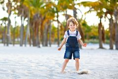 Adorable active little kid boy having fun on Miami beach, Key Biscayne. Happy cute child relaxing, playing with sand and. Enjoying sunny warm day near palms and royalty free stock photo