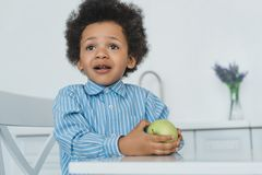 adorable african american boy holding apple at table stock photo