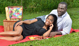 Adorable African American couple on picnic. Cute African-American couple having a picnic in a park - women in black dress men in button up shirt - on red blanket Stock Photos