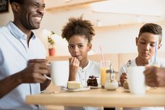 Adorable african-american father and kids. In cafe stock images