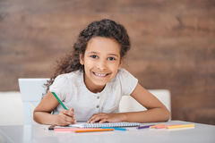 Adorable african american girl drawing with colorful pencils Royalty Free Stock Images