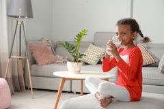 Adorable African-American girl with glass of milk royalty free stock photo