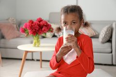 Adorable African-American girl with glass of milk stock photos