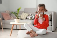 Adorable African-American girl with glass of milk stock images