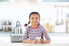 Adorable African-American girl with glass of milk royalty free stock image