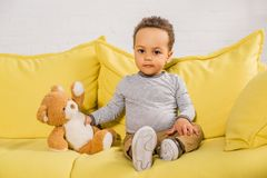 Adorable african american kid holding teddy bear and looking at camera while sitting. On yellow couch stock photography