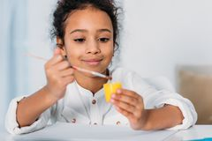 Adorable african american kid putting paint brush into. Poster paint stock photography