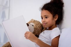 adorable african american kid reading book and hugging teddy bear royalty free stock photography