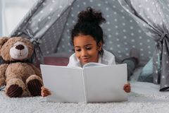 adorable african american kid reading book and lying in tent royalty free stock photos