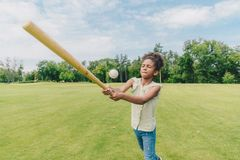 Child playing baseball in park. Adorable african american little girl with baseball bat in hands playing baseball in park Stock Photos
