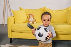 Adorable african american toddler holding soccer ball and remote controller. At home stock image