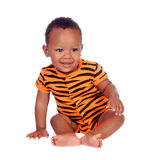 Adorable african baby with with brindle pajamas sitting on the f Stock Photo