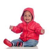 Adorable african baby sitting on the floor with red raincoat Royalty Free Stock Image