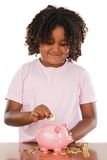 Adorable african girl putting a coin in a piggbank Stock Photography