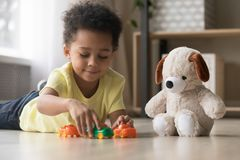 Adorable african kid lying on warm floor play with toys royalty free stock photo
