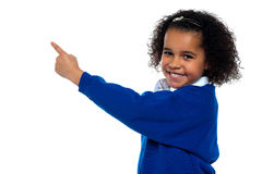 Adorable African kid pointing at copy space area. While facing the camera Stock Photo