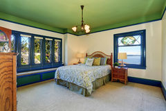 Adorable antique bedroom interior with green ceiling and blue trim. Stock Photography