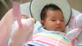 Adorable Asian baby feel sleepy , lying in a swing cradle stock footage