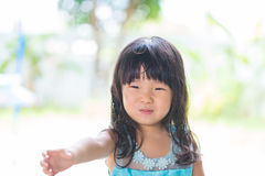 Adorable Asian baby girl in blue dress, on white and green backg Royalty Free Stock Photos